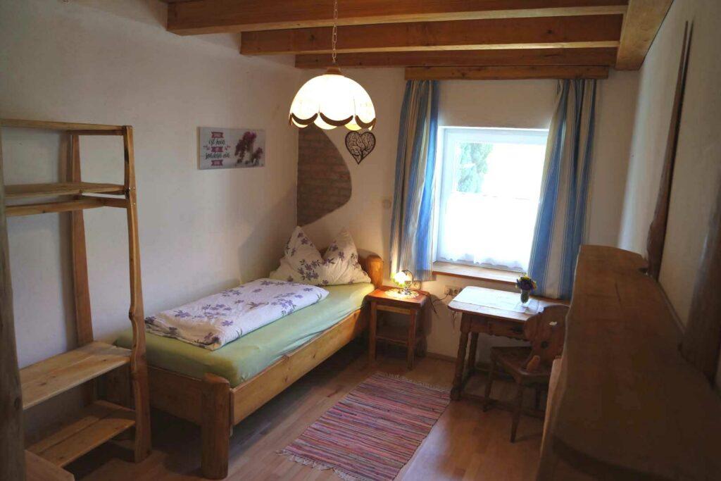 Einzelzimmer mit Bett, Tisch und Kleiderstange