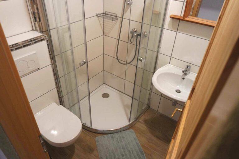 Badezimmer mit Eckdusche, Waschbecken und WC