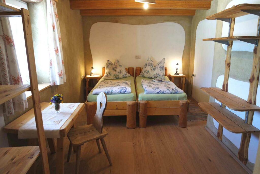 Zimmer mit Doppelbett, Tisch, Kleiderstange sowie Wandregal